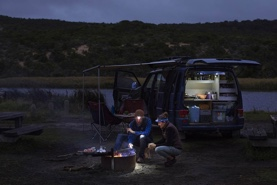 Photo of a couple cooking in front of their van during a road trip through Australia.