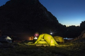 Photo of a family camping, with lighting from Petzl headlamps.